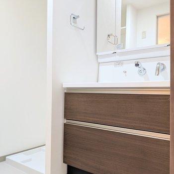 洗面台は3面鏡で身支度もバッチリ。となりに洗濯パン。(※写真は2階同間取り別部屋のものです)
