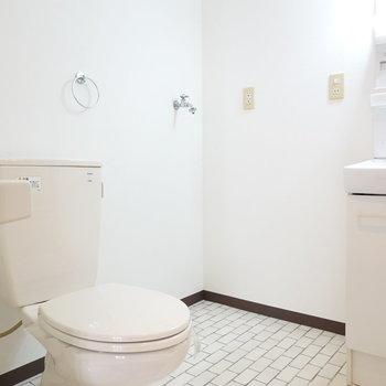 入って左がトイレ。レンガ調の床がカワイイ。洗濯機は奥に設置可能。