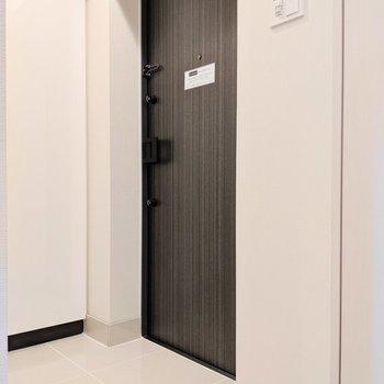 白タイルの玄関※写真は8階の同間取り別部屋のものです