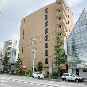 大通り沿いの背の高いマンション。1階にレンタカーのお店が入ってます。
