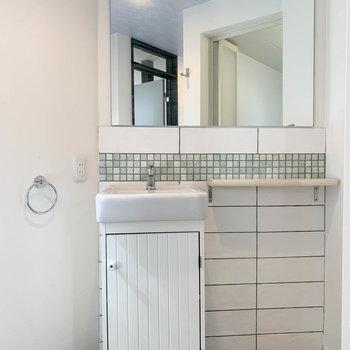 鏡の大きな洗面台。サイドには棚もあります。