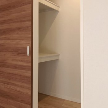 ハンガーポールの向かいには棚。ケースを使って収納したい。