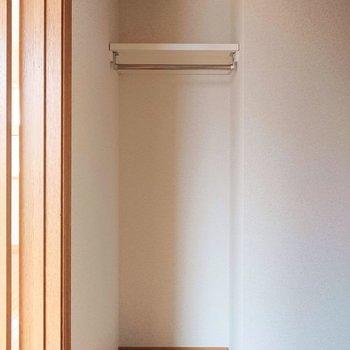玄関扉の向かいに服を掛けるスペース。服以外にも使えるかも。