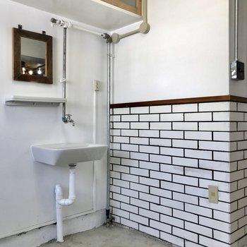 キッチンの横には可愛らしい洗面台、隣の白レンガが爽やか。木の鏡も味があります