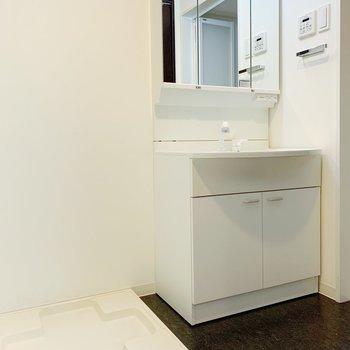 キッチンの向かい側がサニタリー。独立洗面台の鏡を開けるとが収納になっています。(※写真は8階の同間取り別部屋のものです)