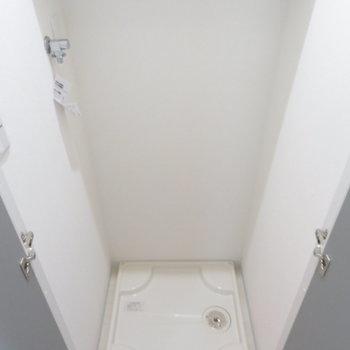 廊下の扉を開ければ洗濯機置き場が(※写真は8階の反転間取り別部屋のものです)
