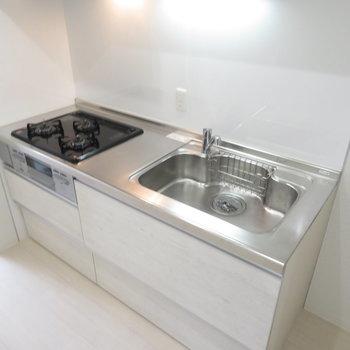 キッチンは3口コンロのシステムキッチンです(※写真は8階の反転間取り別部屋のものです)