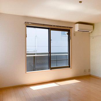 窓の大きい、シンプルなお部屋。右の壁はオリーブカラー。※写真は2階の同間取り別部屋のものです