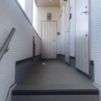 お部屋までは階段で。玄関扉も腰壁と同じ柄なの