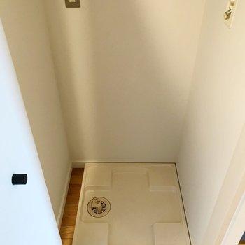 洗濯機置場はキッチンの隣に。扉で隠して生活感を見せない工夫。