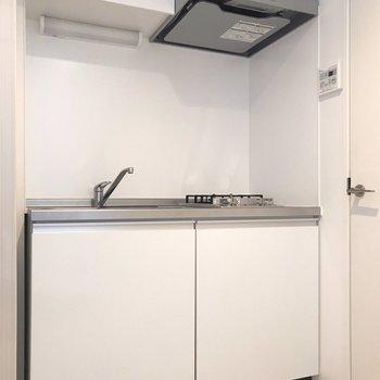 白いキッチンは清潔感たっぷり!隣の扉は脱衣所です(※写真は清掃前のものです)