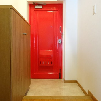 玄関はポップな赤!(※写真は2階の同間取り別部屋のものです)