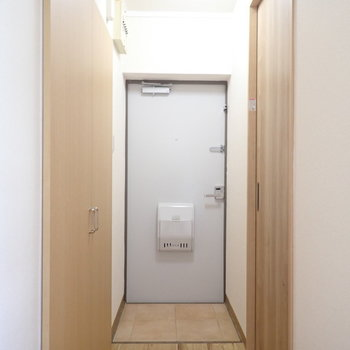 細長い玄関と廊下。左の扉は…