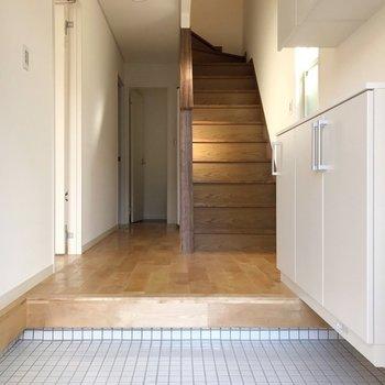 玄関を開けると全体に広がる無垢床と、白いタイルがお出迎え。