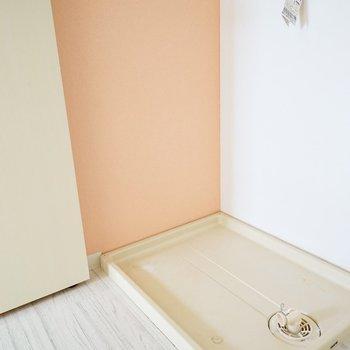 壁のピンクがポイントな、玄関横の洗濯機置場