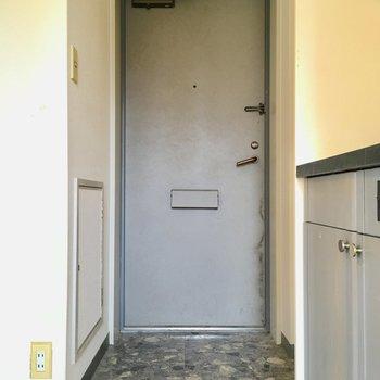 玄関の下足場は石調でシックに。