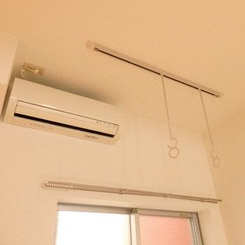 室内物干し竿フック&エアコンも完備(※写真は2階の同間取り別部屋のものです)