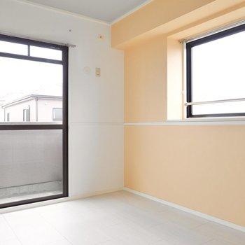 【リビング側洋室】薄いオレンジのアクセントクロスのお部屋です。