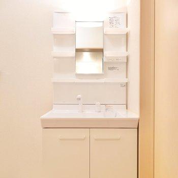 手前には洗面台。居室と合わせた暖色の照明付きです。