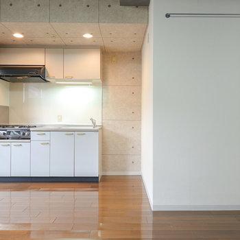 コンクリ風のクロスのキッチン。右の壁にはバー付き。