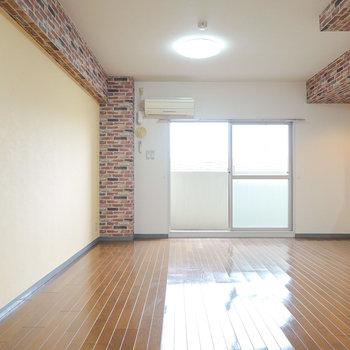 柱部分にレンガ調のクロスがあしらわれた14.6帖の洋室。