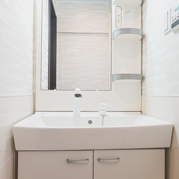 脱衣所内には棚付きの洗面台。