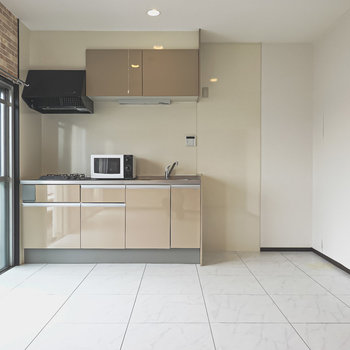 対面側にはキッチン。ツヤッとしたパネルが大理石調の床にピッタリな雰囲気。