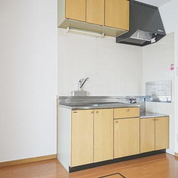 木調パネルの明るいキッチン。冷蔵庫置き場は左手に。