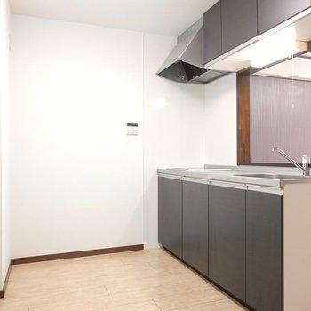 黒で引き締められた印象のキッチン。家電やラックは後ろのスペースに。