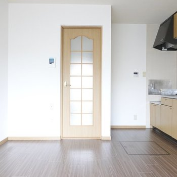 扉の先はトイレなど水回りと2階への階段があります。