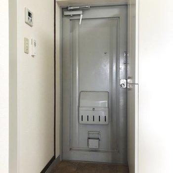 扉の塗装がレトロな玄関。※写真は2階の同間取り別部屋のものです