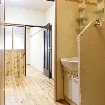 玄関から見た景色。洗濯機置場と洗面台の間の壁、漆喰が塗られています。(※写真は清掃前のものです)