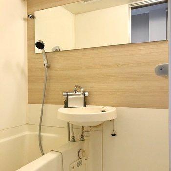 お風呂は2点ユニット。横長の鏡と木目のクロスがポイントです。