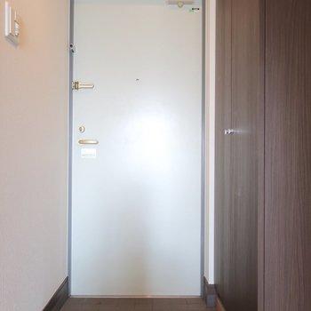 玄関もブラウンベースで落ち着いた印象(※写真は11階の反転間取り別部屋、清掃前のものです)