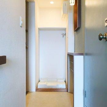 洗濯機置き場は玄関に。ロールカーテンで隠す事もできます。