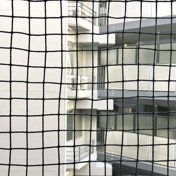 鳥除けネット越しのマンションビュー。