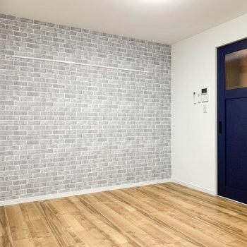 【洋室】窓のサイド、こちらはレンガ調の壁紙でアクセント。青い扉は廊下へ続きます。