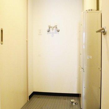 キッチンの奥には脱衣所が。シックな床。※写真は同間取り反転タイプ