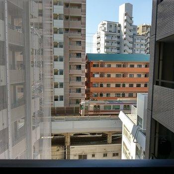ビルの隙間から電車が見え隠れ。ほっこりする風景。