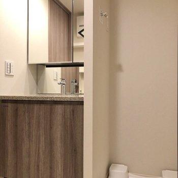 鏡部分が収納になっている洗面台と洗濯機置き場が並びます。※写真は5階の同間取り別部屋のものです