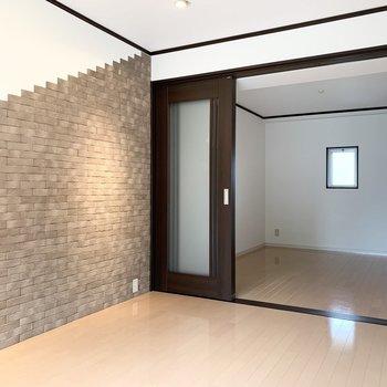 アクセントウォールのむこうに洋室。引き戸で間仕切りなので大きく1つの空間としても。
