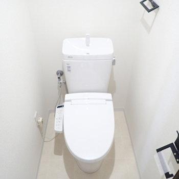 トイレは白い空間。ホルダーのデザインがおもしろい。