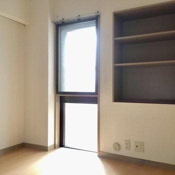 こちらは玄関横の4.5帖の洋室。本棚にも使えそうな棚はビルドイン。(※写真は6階の同間取り別部屋のものです)