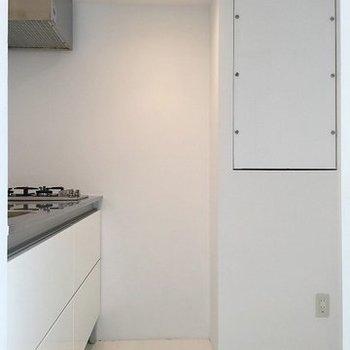 キッチンの後ろに洗濯機と冷蔵庫の置くスペースあり。※写真は702号室のもの