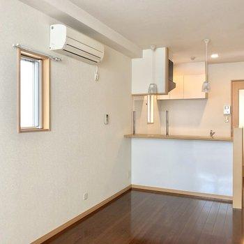 角部屋だから、窓がこちらにも。ダークブラウンの床が落ち着いた雰囲気にしてくれる。