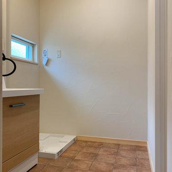 脱衣所の奥に換気窓と、洗濯機置き場。