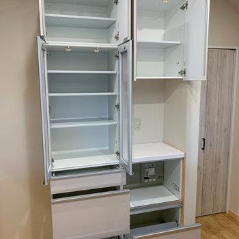 【キッチン】後ろには食器棚。炊飯器や電子レンジを置ける場所もあります。そして食器棚の右には扉。