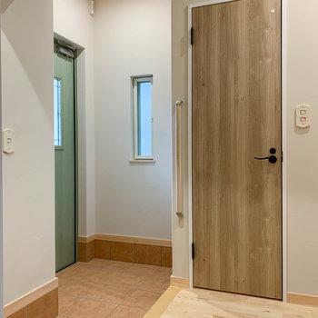 6.1帖の洋室を出て、玄関周辺へ。濃い木の扉はトイレです。