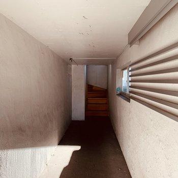 建物にはココを抜けて階段を上がり入ります