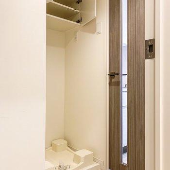 洗濯機置場はお部屋の手前に。上部棚には洗剤などがしまえますね。